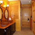 Master bath with cedar paneling milled on site with pebble tile flooring